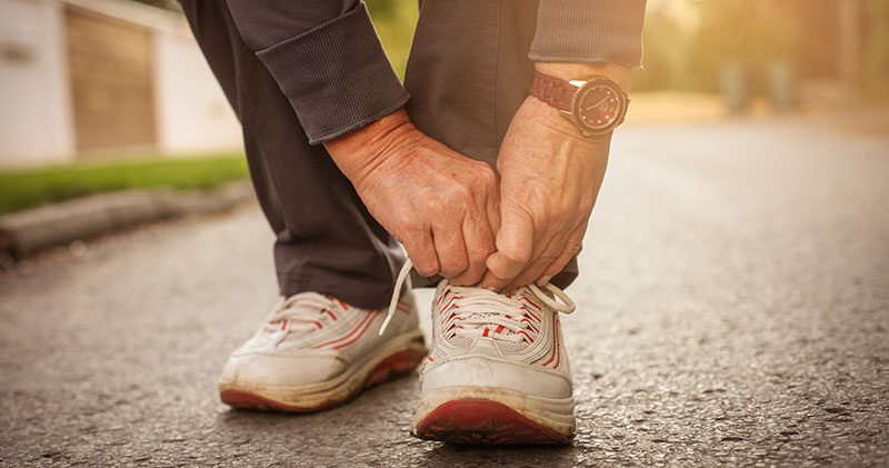 Senior tying shoes before walk in the park.